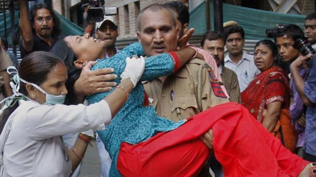 Another victim ... a policeman carries a wounded woman from the blast site outside the High Court in Delhi.