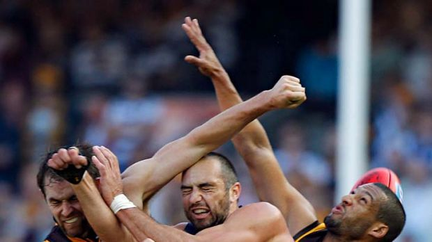 Cats forward James Podsiadly is crunched in a marking contest with Hawks defenders Luke Hodge (left) and Josh Gibson ...