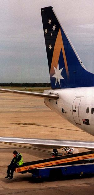Tail of woe ... an Ansett ground crew member sits on a freight conveyor after news of the airline's closure in the ...