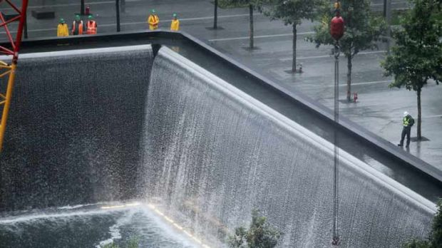 Ground zero ... Workers stand at the north pool waterfall as construction continues on the National September 11 ...