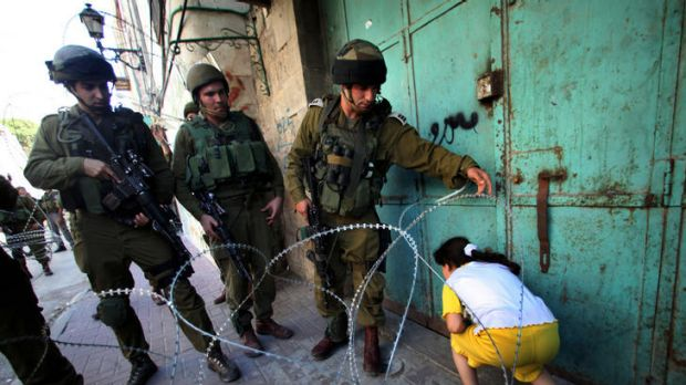 Israeli soldiers let a Palestinian girl make her way past a barbed wire barricade set up to prevent protesting ...