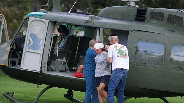 Medics help injured bystanders out of a helicopter into a medical after a plane crashed into the crowd at the Reno ...
