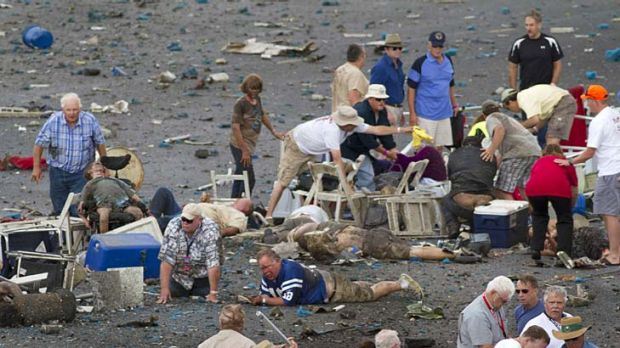 People rush to help injured spectators following the crash of a vintage World War Two P-51 Mustang at the Reno Air Races.