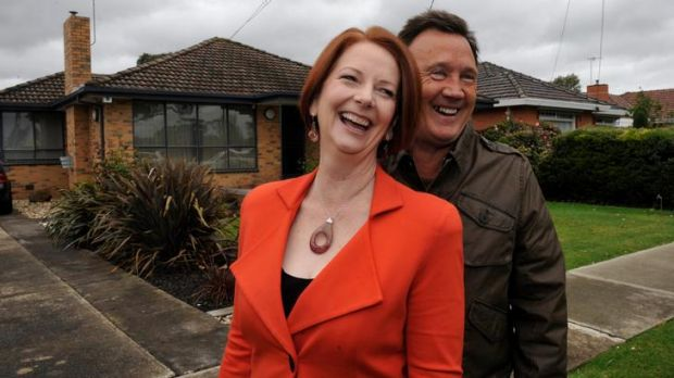 At home with Julia, the Prime Minister and partner Tim Mathieson laugh as a neighbour plays Happy Birthday on a trumpet.
