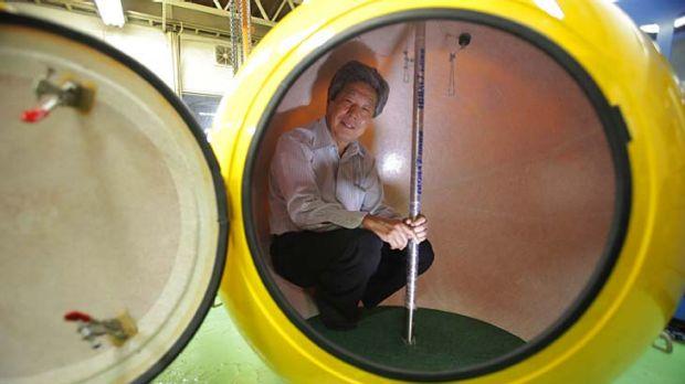"Cosmo Power Co. President Shoji Tanaka inside the spherical earthquake and tsunami shelter ""Noah"" made of fibre enforced ..."