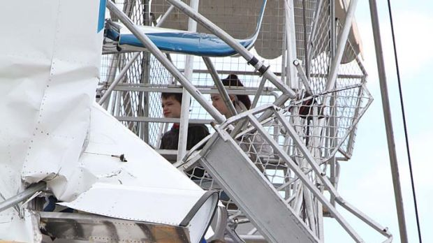 Pilot and passenger and two children await rescue after the ultra-light crashed into a ferris wheel at a country fair ...