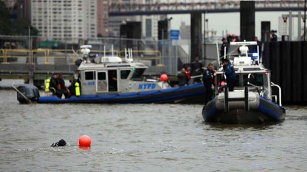 Sydney woman dead ... rescue divers search the East River.