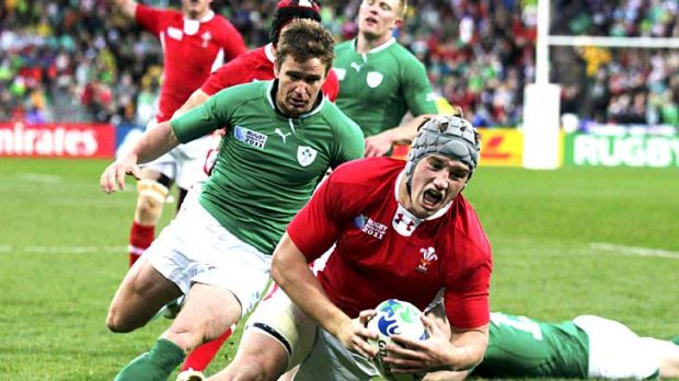 Sloppy defence ... Jonathan Davies scores a try for Wales after beating four Ireland players.