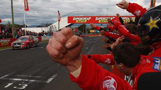 Close finish ... Holden's pit crew celebrates as Garth Tander crosses the line just ahead of rival Craig Lowndes.