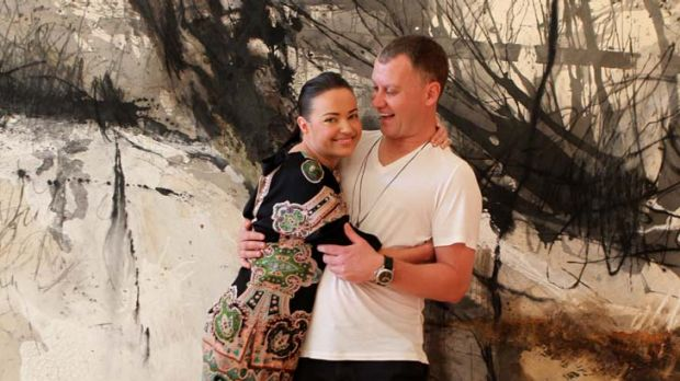 The price of love … Felicity Smith and Paul Lowe with the $12,000 Sophie Cape painting they are asking wedding ...