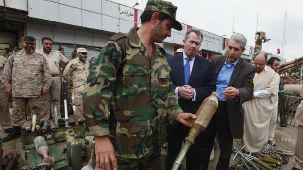 An anti-Gaddafi fighter shows off captured weapons to British Defence Secretary Liam Fox during a visit to Misrata, 200 ...