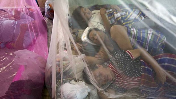 Thais rest under mosquito nets at a makeshift evacuation centre as flooding causes havoc in Ayutthaya.