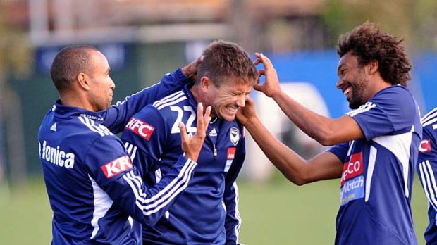 Ear, ear lads: Archie Thompson (left) and Isaka Cernak flick Harry Kewell's ears after the Victory star muffed a kicking ...