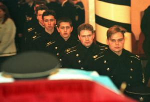 Cadets file past an officer's coffin.
