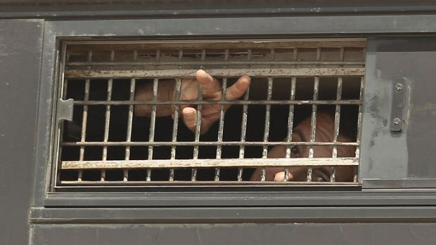 A Palestinian prisoner waves from the window of a bus as it leaves Nafha Prison, Mitzpe Ramon.