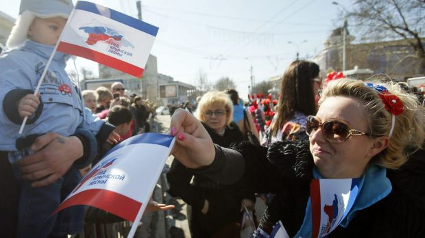 A woman distributes flags during a theatrical performance in Simferopol on Saturday to mark the first anniversary of ...