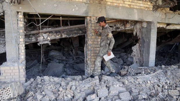 A soldier inspects the demolished tomb of former Iraqi president, Saddam Hussein in Tikrit, Iraq.