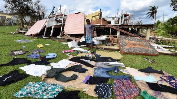 Adrian Banga's clothes lie on the ground as he stands in front of his destroyed house.