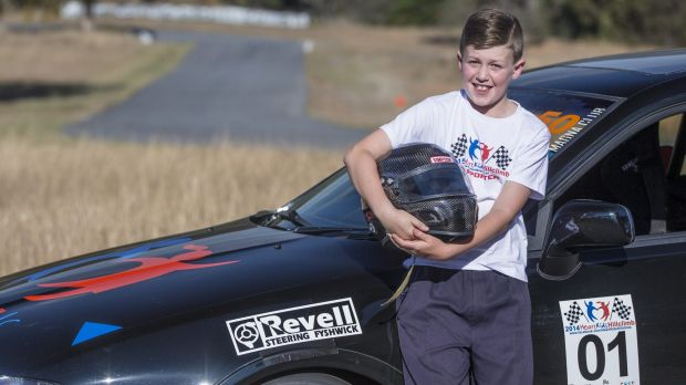 Thomas Henderson-Smith,10, with HeartKids hillclimb organiser Dan Cummin's race car.