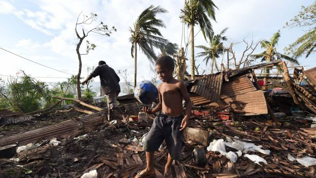Grim aftermath: A child walks through the ruins of his family home with his father Phillip, on March 16 in Port Vila ...