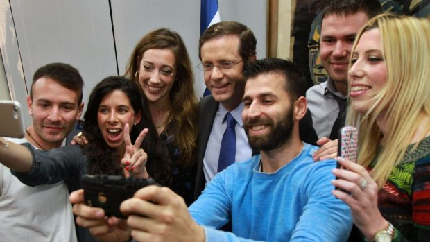 Zionist Union leader Isaac Herzog, centre, poses for a photo with voters in Tel Aviv.