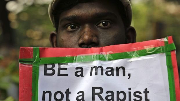 A man holds a placard as Indian Christians and others condemn the gang-rape of a nun at a Christian missionary school in ...