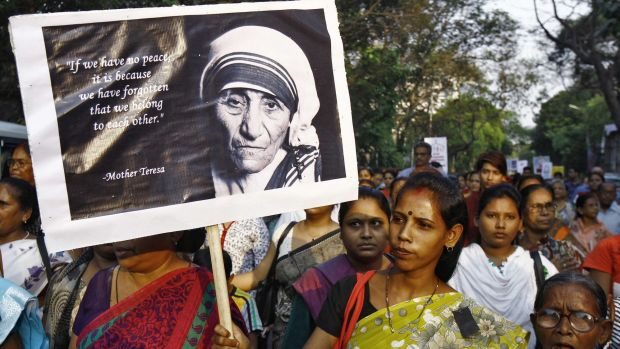 A woman holds a poster of Mother Teresa during a vigil. Christians in India said on Monday that the Hindu nationalist ...