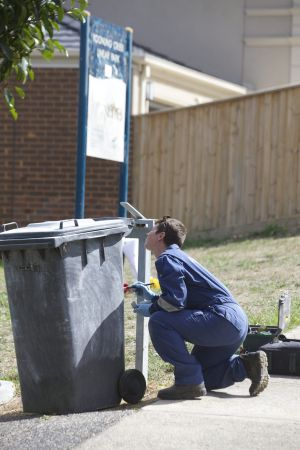 A forensics police officer dusts a bin that sits near the scene were the teenager was stabbed to death.
