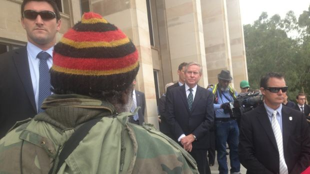 An Aboriginal elder approaches a heavily-guarded Colin Barnett.