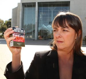 Former attorney-general Nicola Roxon holds a pack of cigarettes with plain packaging.