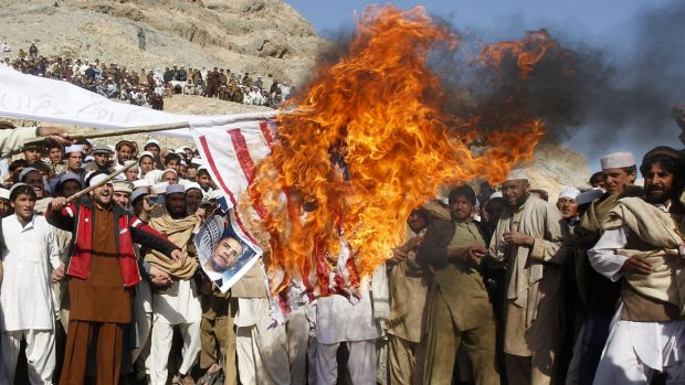 Afghan protesters burn a US flag during a protest in Jalalabad province in Afghanistan in February 2012 against the ...