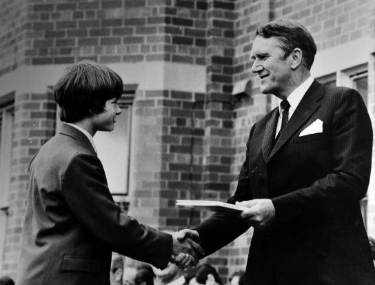 Former Prime Minister Malcolm Fraser presents a prize for consistent effort to T.J. Kimpton at Canberra Grammar school. ...