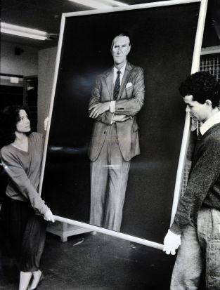 A portrait of Former Prime Minister Malcolm Fraser by Bryan Westwood being moved by National Gallery staffers Sara Kelly ...