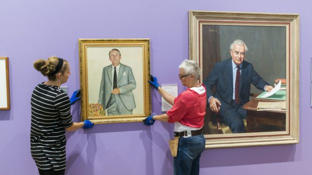 National Portrait Gallery staff hang a portrait of Malcolm Fraser next to a portrait of Gough Whitlam on Friday.