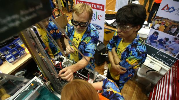 Robots kicking goals: Thunder's pit crew make repairs after a match.