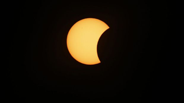 The moon starts to block the sun during a solar eclipse seen from Svalbard, Norway.
