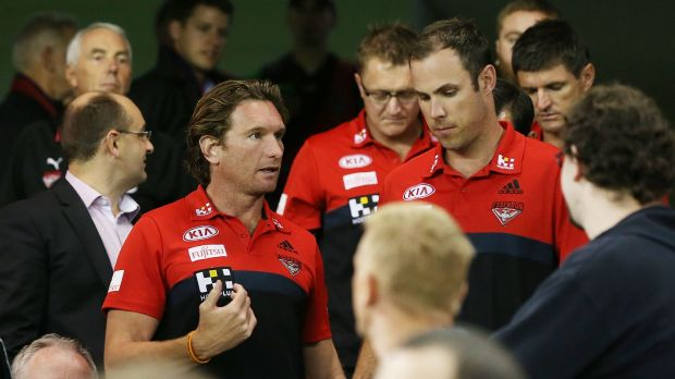James Hird talks to assistant coach Matthew Egan as he leaves the coaches box during a break in the game.
