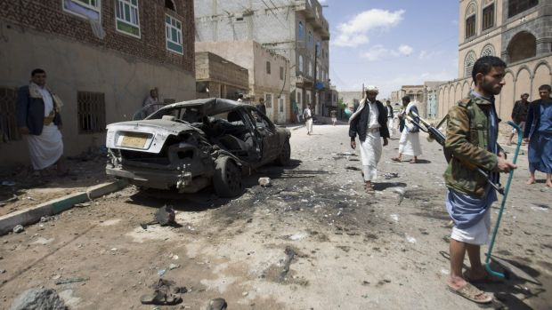 Shiite rebels, known as Houthis, stand near a damaged car after the bombing in Sanaa.