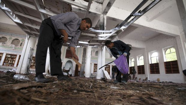 Crime scene investigators search for evidence on the floor after a suicide bomb attack at a mosque in Sanaa.
