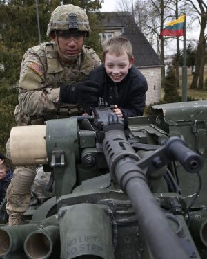 A member of the US Army's 2nd Cavalry Regiment shows a gun to a young boy on a Stryker vehicle during the ''Dragoon ...