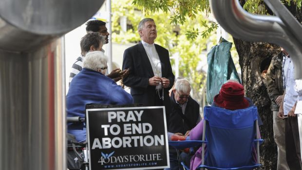 Catholic Archbishop of Canberra and Goulburn Christopher Prowse, centre, attends a prayer vigil outside the ACT Health ...