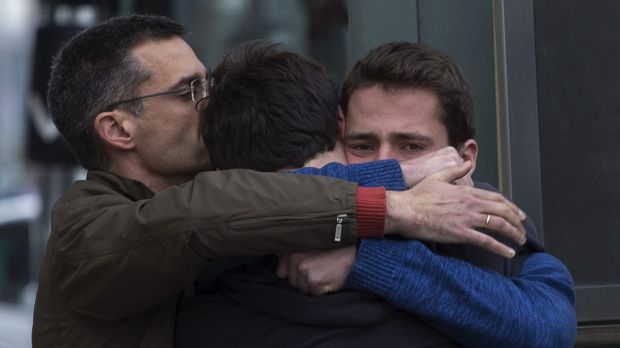 Family members of people involved in the Germanwings plane crash comfort each other as they arrive at Barcelona airport ...