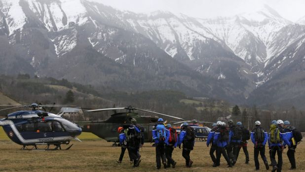 French Police and Gendarmerie Alpine rescue units gather on a field as they prepare to reach the crash site.