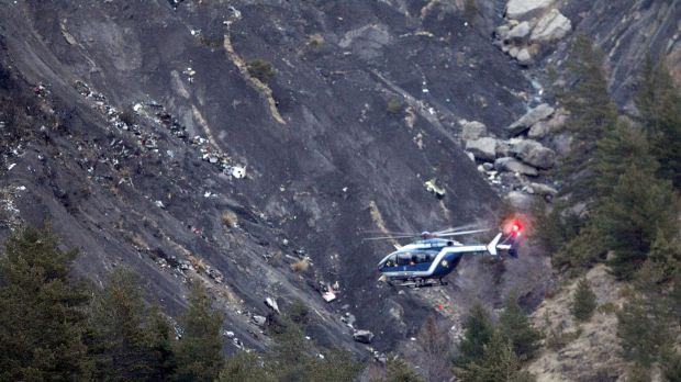 A rescue helicopter flies over debris of the Germanwings passenger jet, scattered on the mountainside, near ...