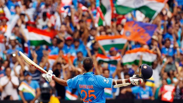 India's Shikhar Dhawan acknowledges supporters in the crowd as he celebrates after reaching a century during a Cricket ...