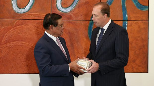 Immigration Minister Peter Dutton gives a present to Cambodian Deputy Prime Minister and Minister of the Interior Sar ...
