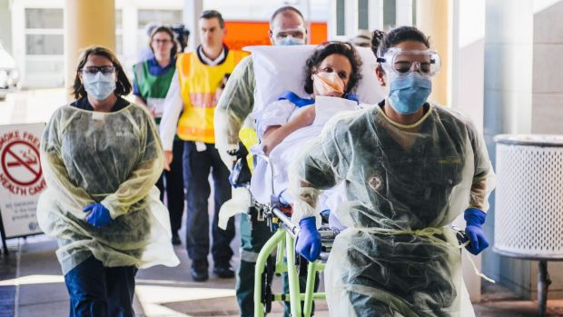 A patient arrives at Canberra Hospital by ambulance from Calvary as part of an Ebola training exercise.