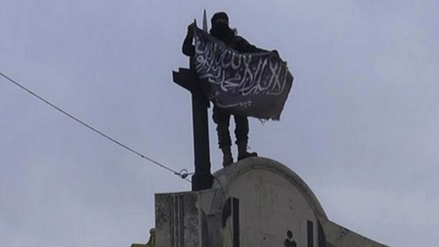 Something to fight for: a militant from Syria's al-Qaeda-linked Nusra Front holds his group flag in Idlib province, ...