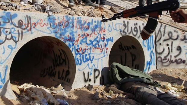 Last stand ... an anti-Gaddafi fighter points at the drain where Muammar Gaddafi was reportedly hiding before he was ...