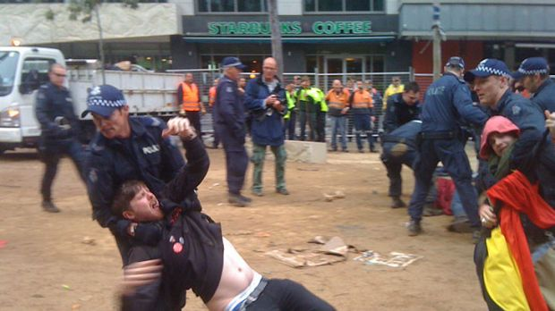 A man is dragged out of City Square by force.